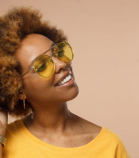 African female model studio shot isolated on brown backrgound with copy space for your text, smiling