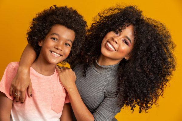 Portrait of young African American mother with toddler son. Yellow background. Brazilian family.